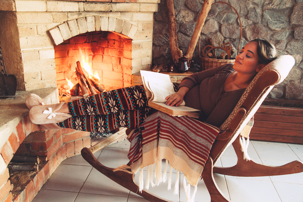 Woman enjoy her cabin rental vacation by the fireplace